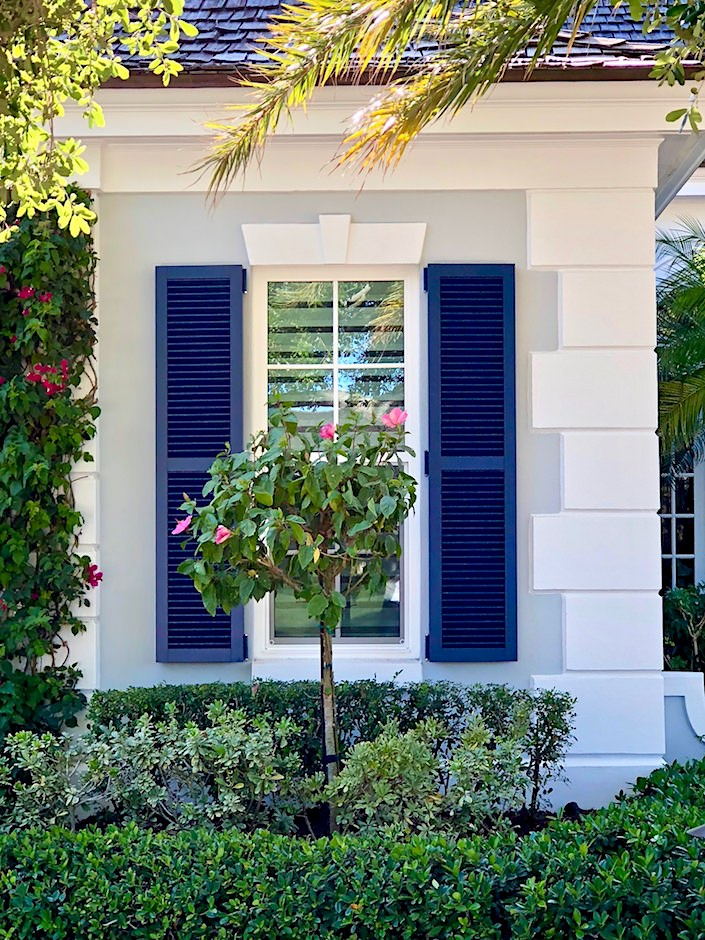 blue shutters against gray Florida exterior